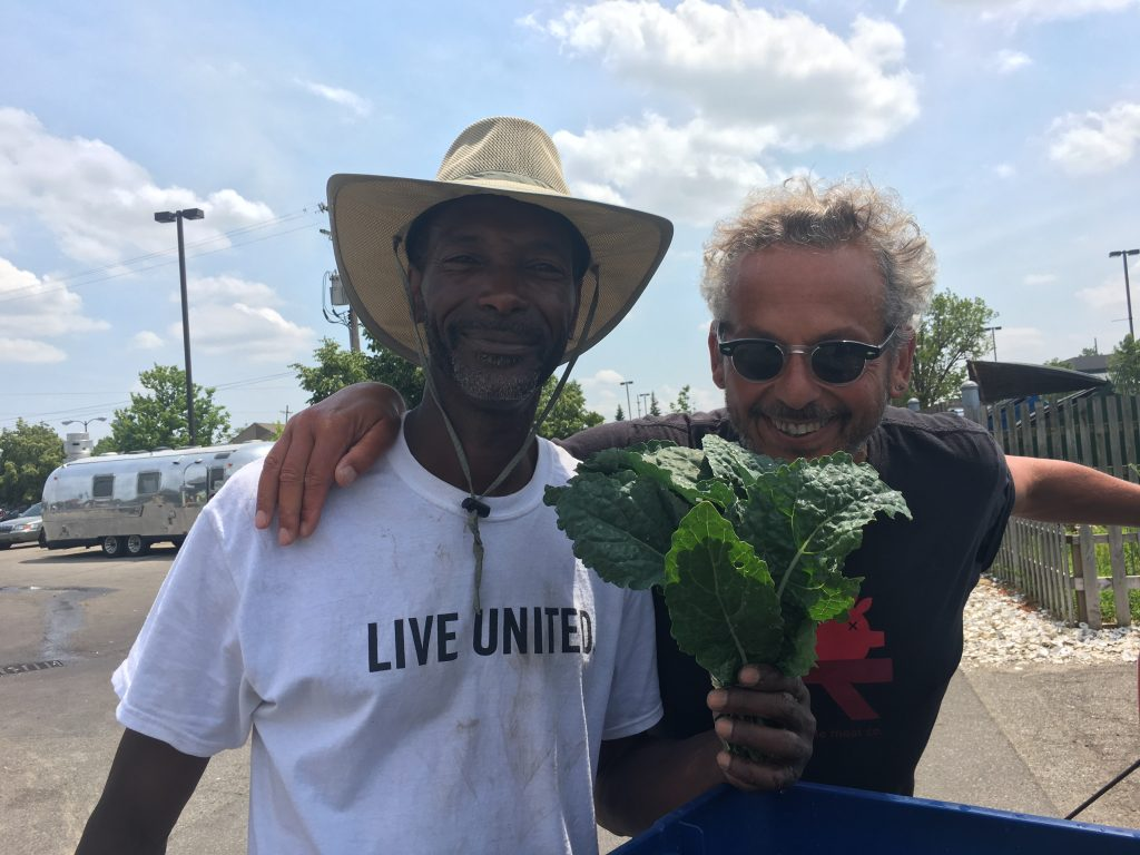 Melvin Parson and Ari Weinzweig smiling together with a bunch of leafy greens.