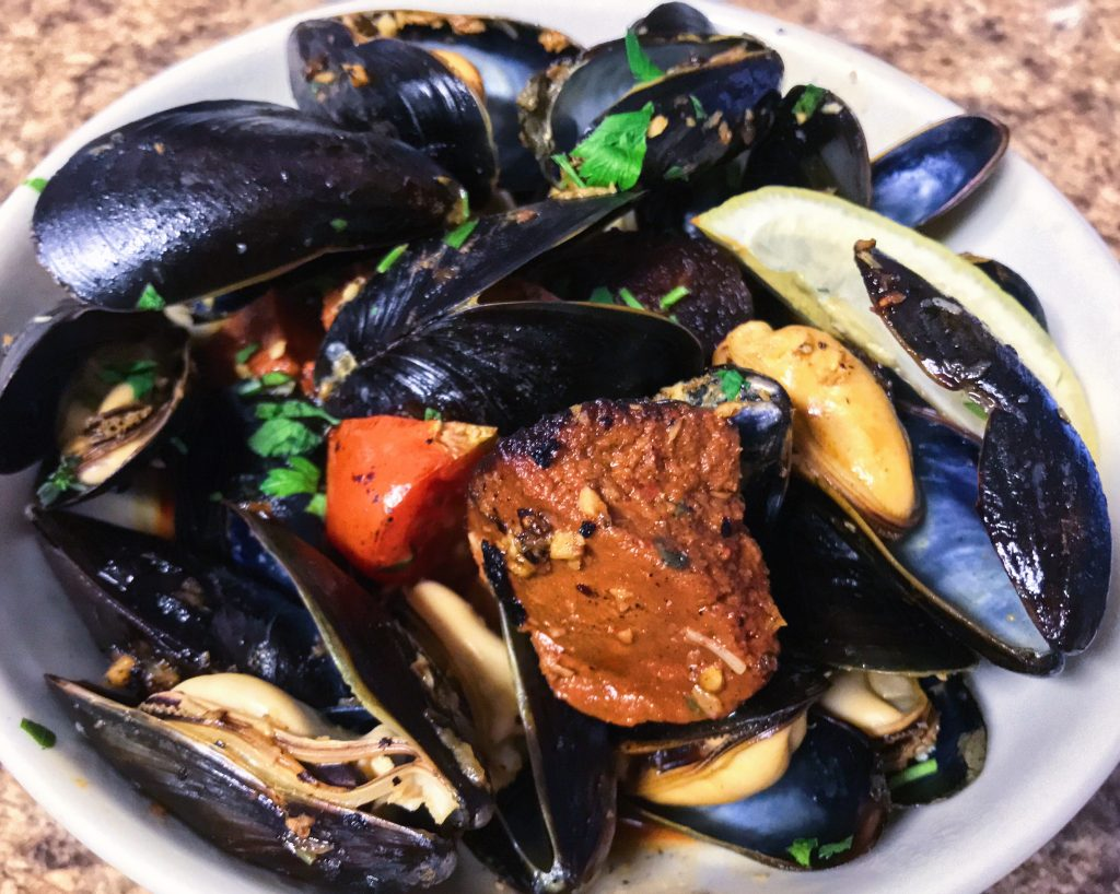 Bowl of steamed mussels with 'Nduja sausage and tomatoes.
