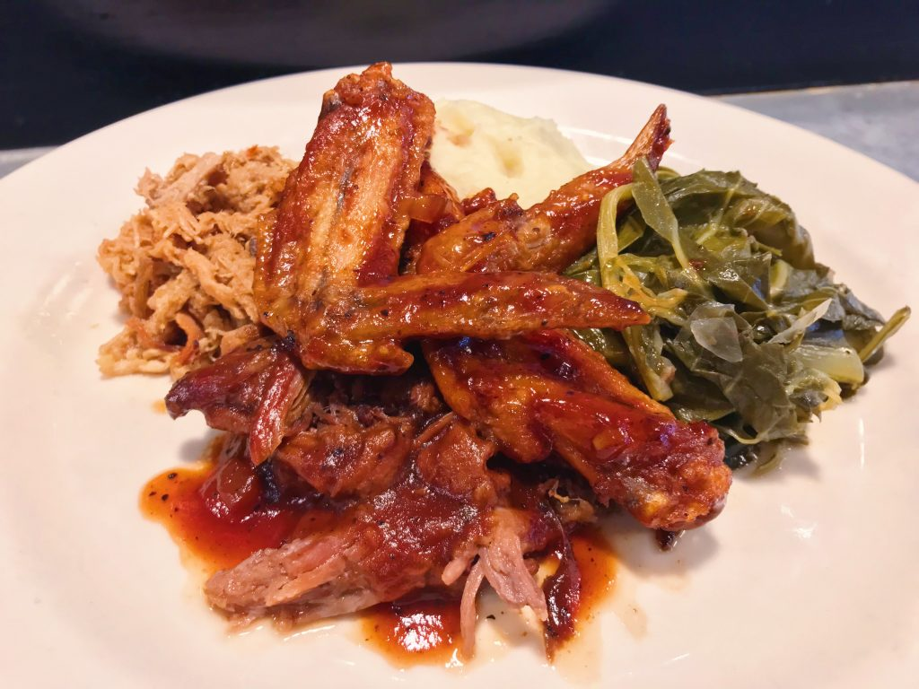 Roadhouse BBQ plate, with pit-smoked pork and beef, BBQ wings, braised greens, and mashed potatoes.