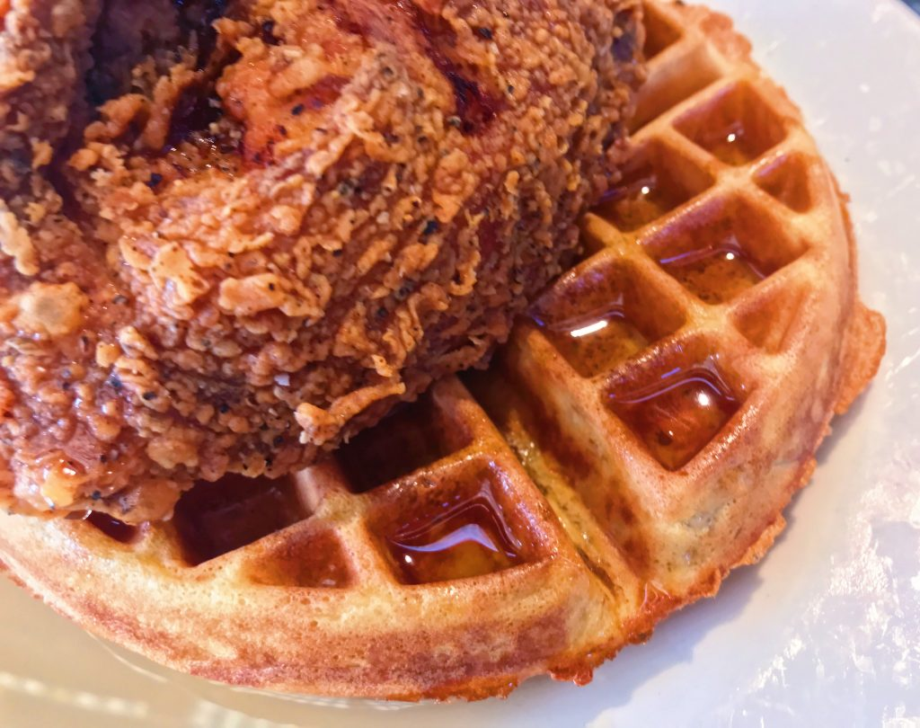 Golden Belgian waffle topped with crispy fried chicken breast and maple syrup.
