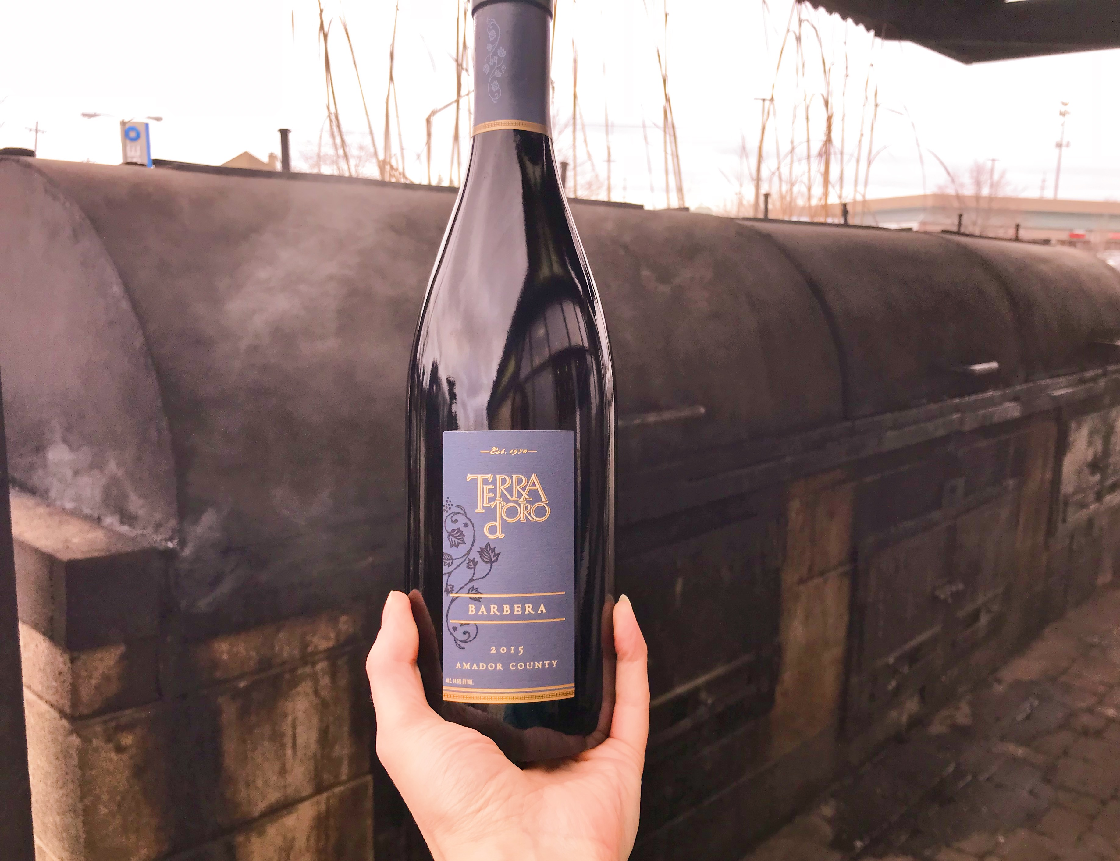 A bottle of Terra d'Oro Barbera held in front of the pit smoker at Zingerman's Roadhouse.