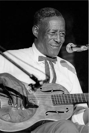 A photo of Son House playing the guitar at the Ann Arbor Music Festival in 1969.
