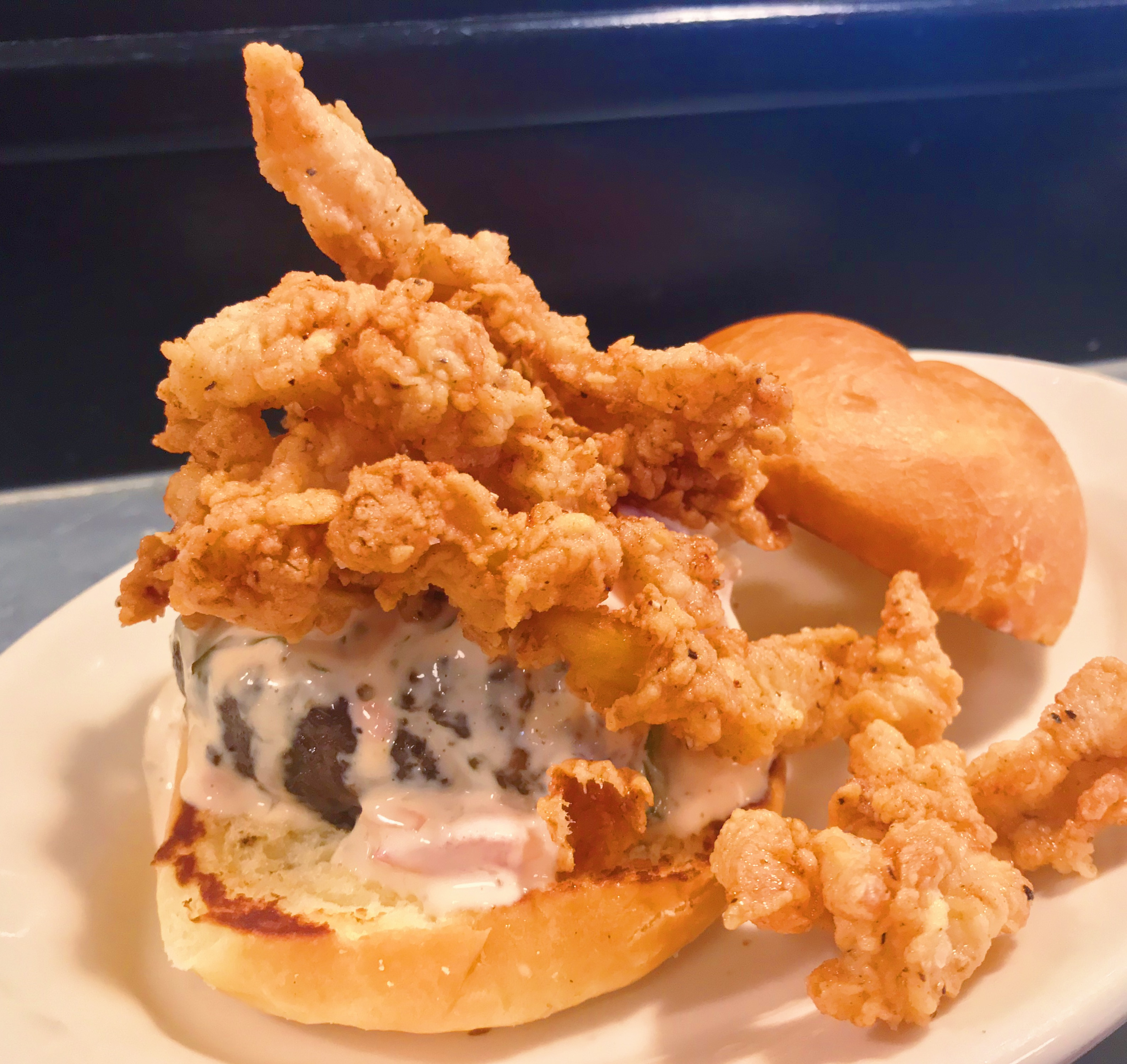 A Roadhouse burger topped with fried clams and tartar sauce.
