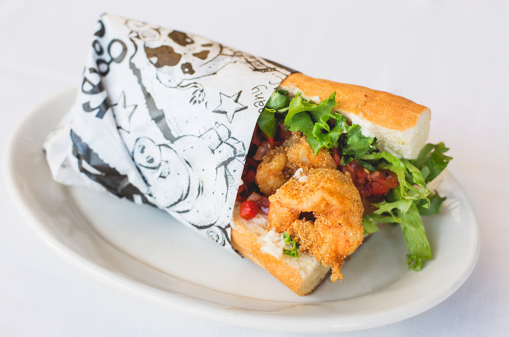 Shrimp Po'Boy with fried shrimp, lettuce, tomato relish, and mayo on a soft baguette.