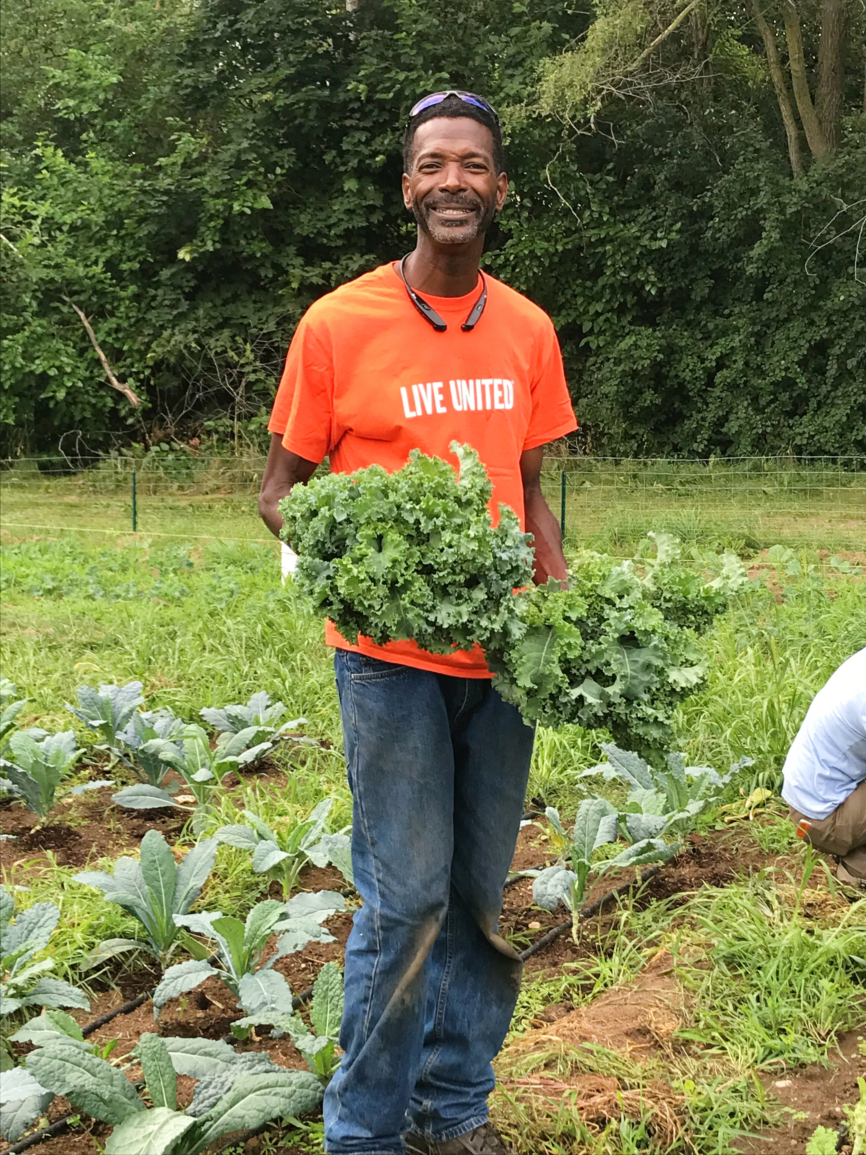 Farmer Melvin Parson holding a bunch of kale at his farm in Ypsilanti.