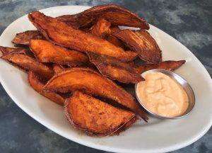 A plate of sweet potatoes with curry spice and spicy mayo