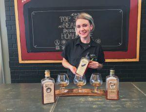 A Zingerman's Roadhouse bartender, Lauren Grant, with the Journeyman Distillery whiskey flight.