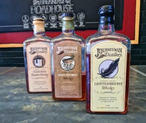 In order of the flight, bottles of whiskey from Journeyman Distillery: Featherbone Bourbon, Buggy Whip Wheat, and Last Feather Rye.