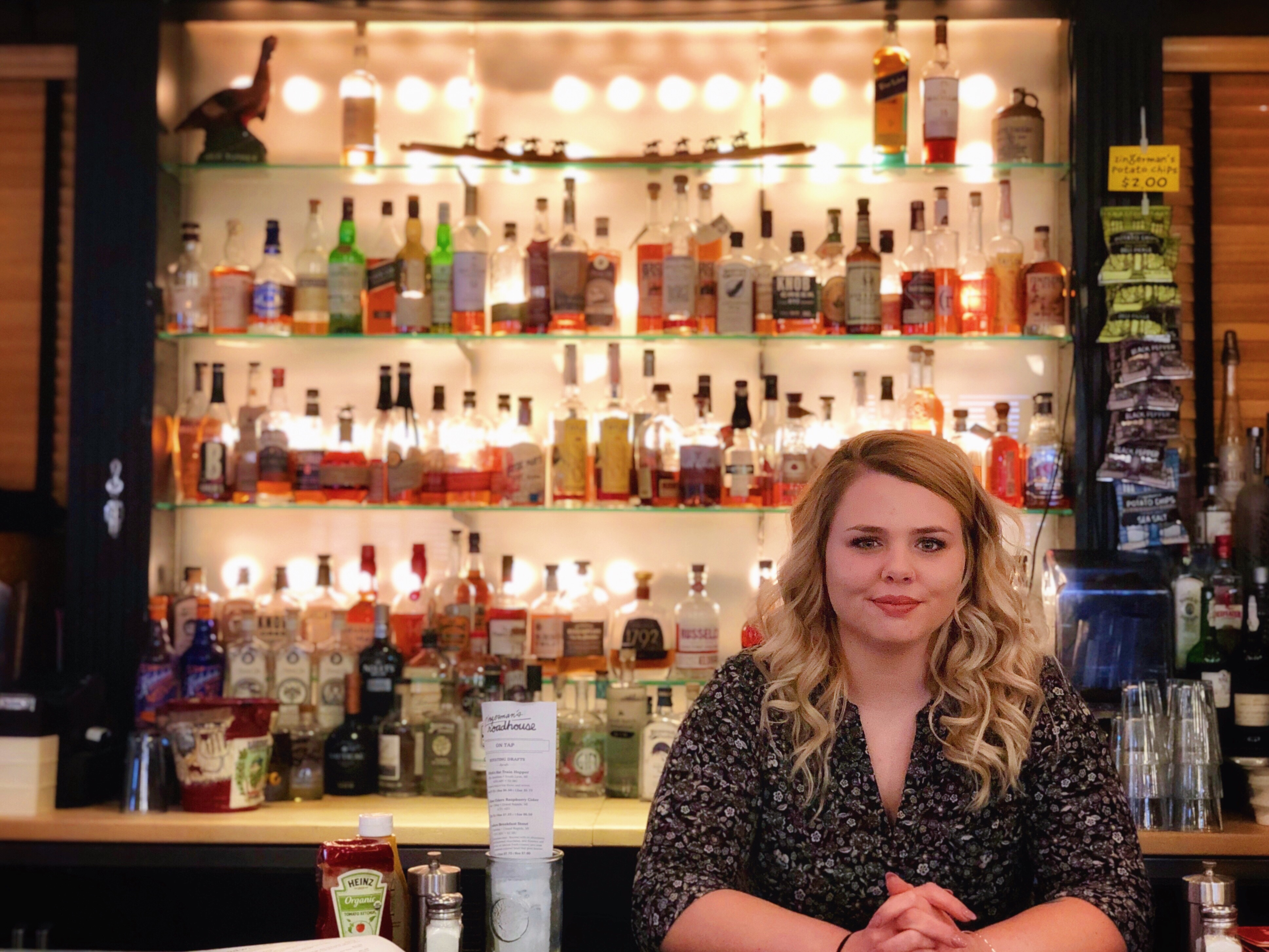 Roadhouse Bar Manager, Sarah Bartlett, in front of shelves of whiskey and bourbon.