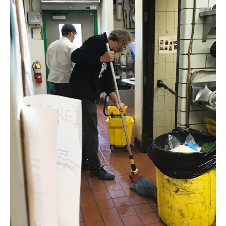 Ari Weinzweig, Zingerman's CEO, mops the current kitchen floor at Zingerman's Roadhouse.