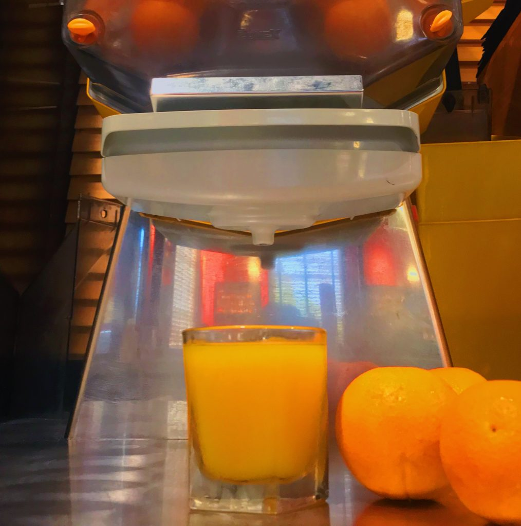 A glass of freshly squeezed orange juice in front of a large, state of the art juicer at the Roadhouse.
