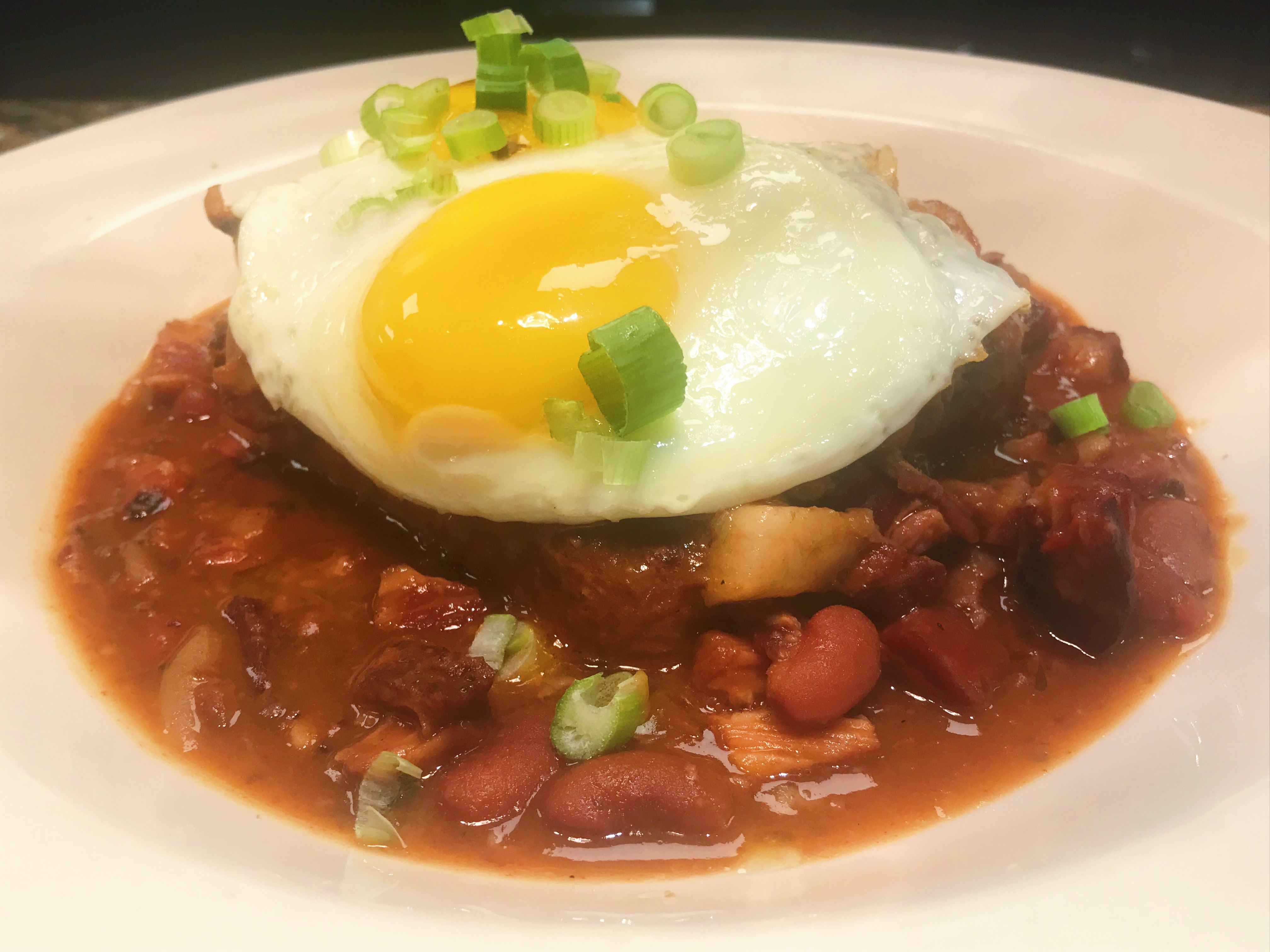 Baked red beans on toast with sunny-side-up eggs.