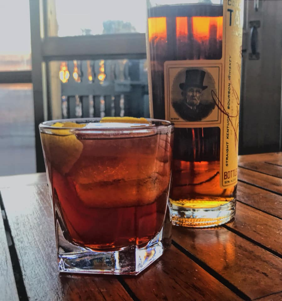 A bottle and a glass of Colonel E.H. Taylor small batch bourbon.