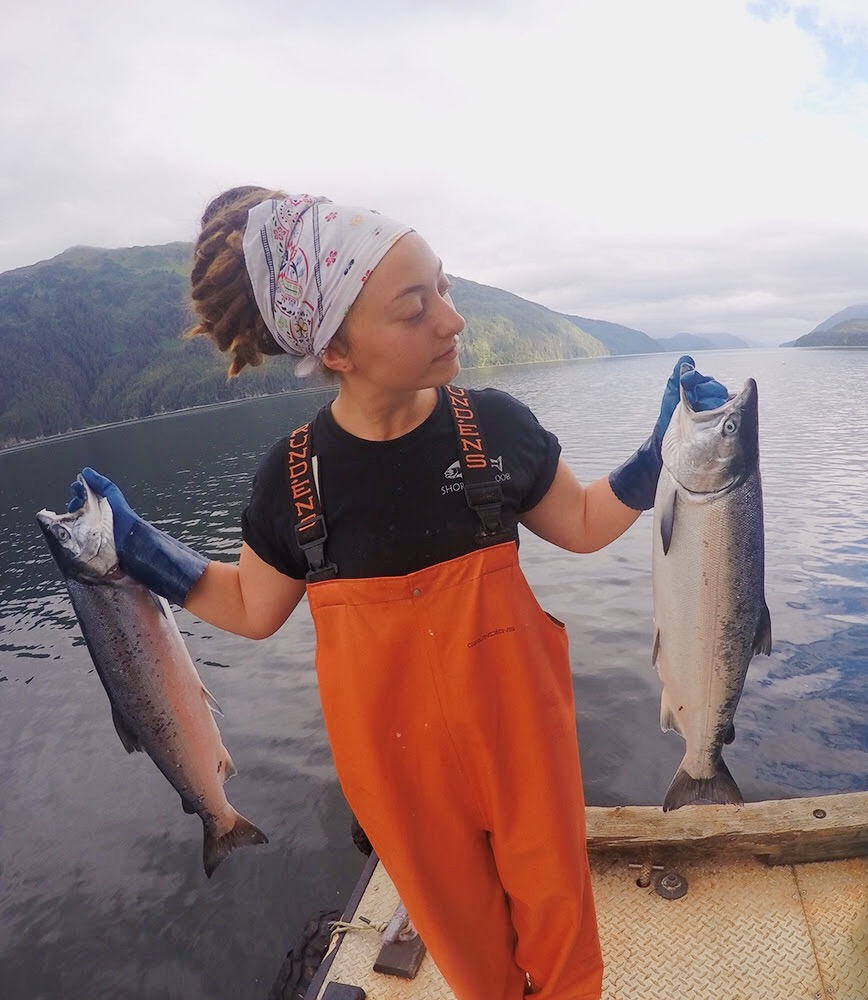 Marie Rose from Shoreline Wild Salmon, holding two freshly caught salmon.