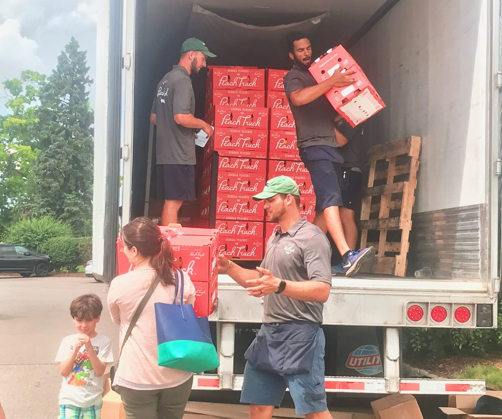 The Peach Truck unloads 25lb boxes of peaches for the guests waiting in the Roadhouse parking lot.
