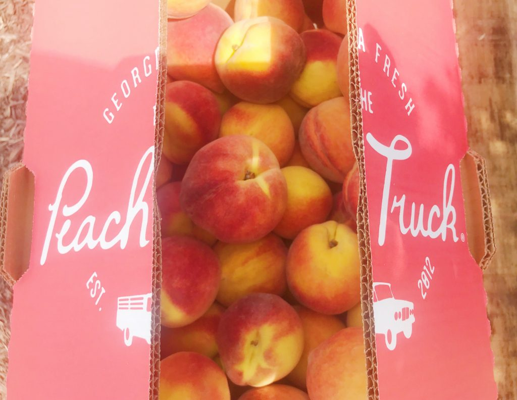 A box of peaches with the Peach Truck logo on the top, opened to reveal the peaches inside.