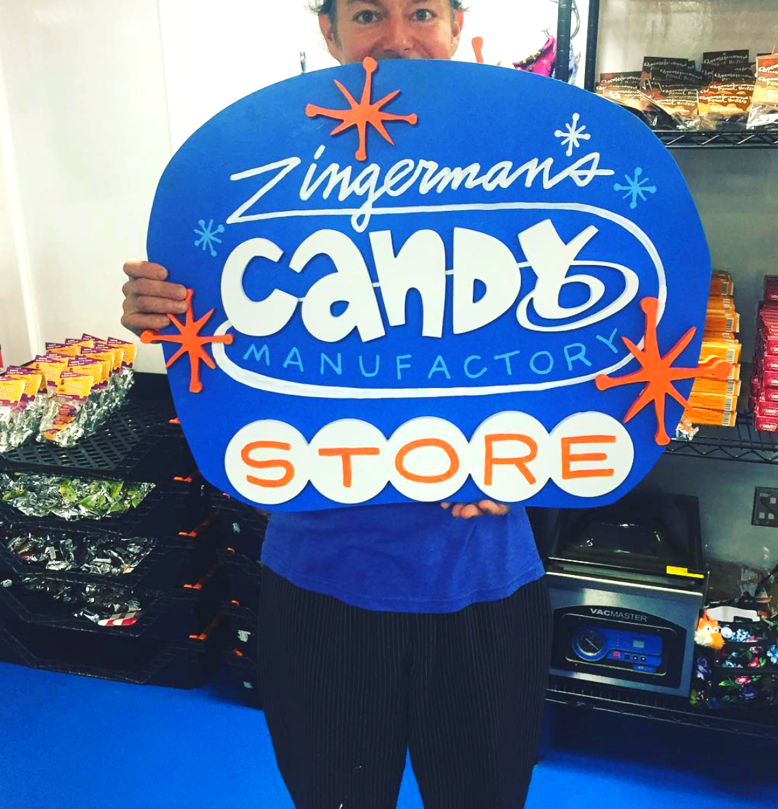 Charlie Frank holding up the sign for the Zingerman's Candy Manufactory Store.