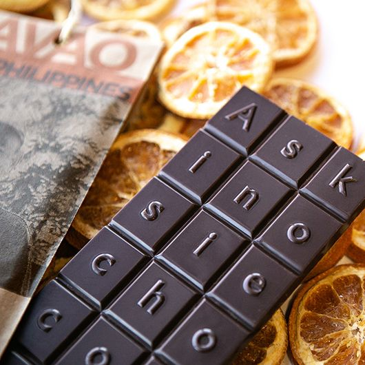 An Askinosie chocolate bar surrounded by orange slices.