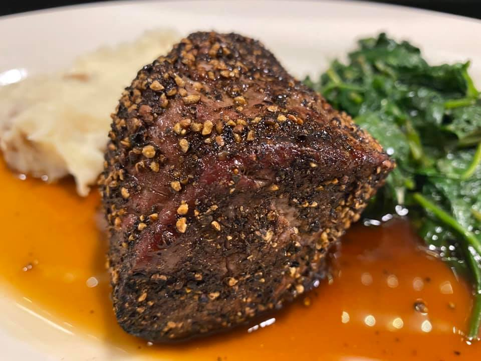 A sirloin cut coated with Épices de Cru Tellicherry black pepper, plated with au Poivre sauce, spinach, and potatoes.