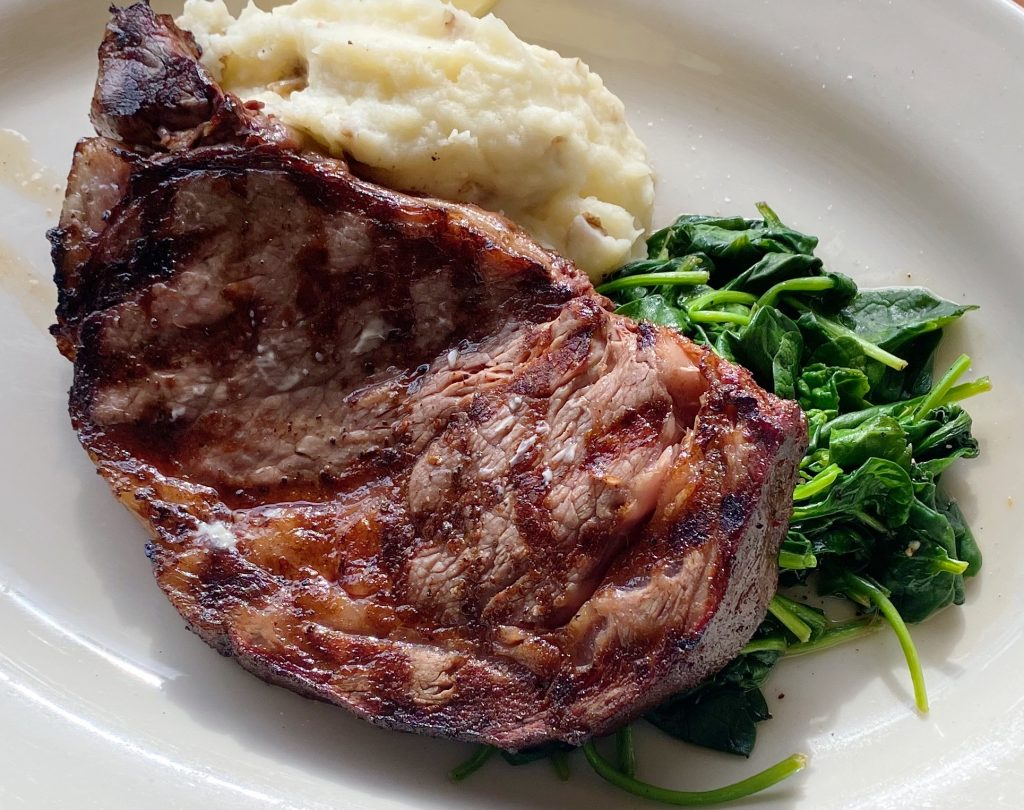 Smoked ribeye with sautéed spinach and mashed potatoes.