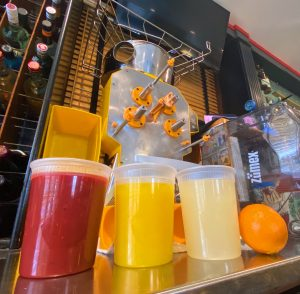 Quarts of freshly squeezed juices in front of a large juicer.