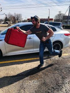 A Roadhouse delivery server holding a carry out bag by his car.