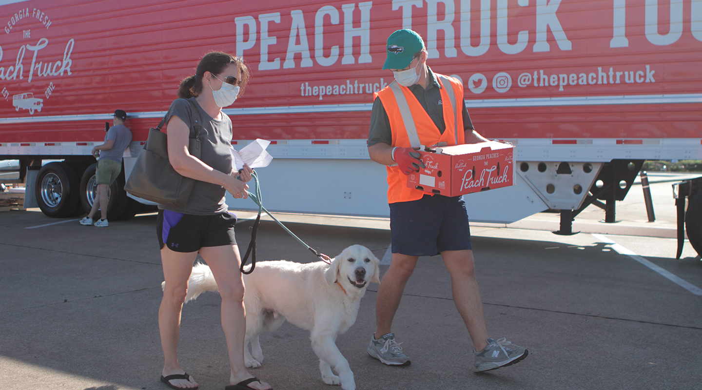 A Peach Truck staffer walks with a guest and her dog, carrying a box of peaches.