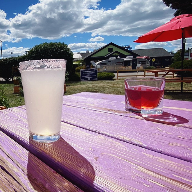 A margarita and a strawberry daiquiri on a colorful picnic table by the Roadhouse.