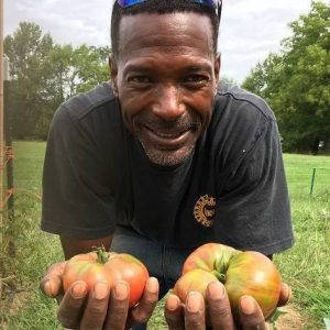 Melvin holding two heirloom tomatoes at his farm