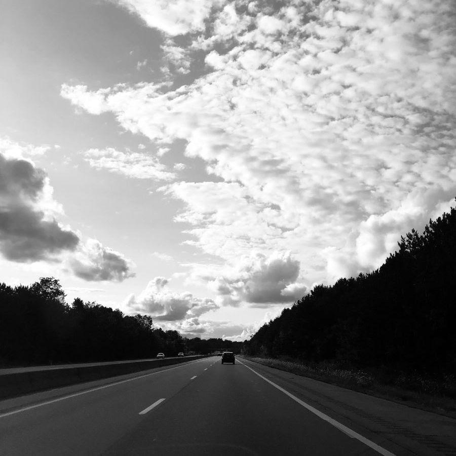 A car drives off down a long road.