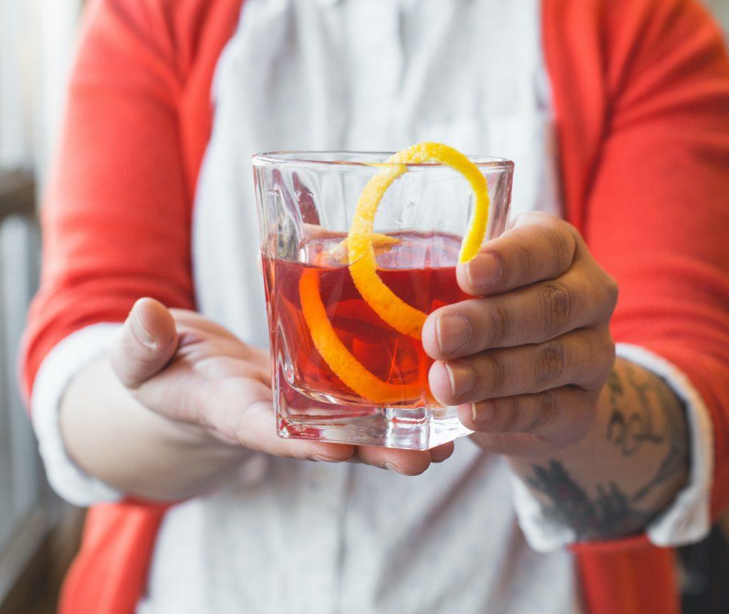 A Roadhouse employee holds a glass of Sazarac.