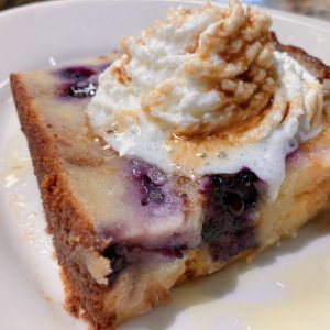 A housemade biscuit and blueberry bread pudding with whipped cream.