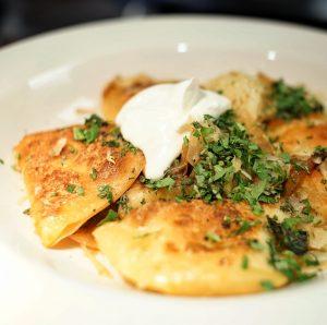 A plate of potato pierogi with sour cream.